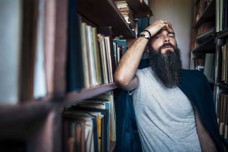 Thoughtful hipster man among bookshelves
